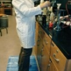 Scientist lab worker standing on top of Marbleized Blue Tile Top Anti-Fatigue Mats in a laboratory setting
