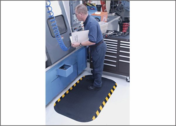 "Man standing on a 5/8"" thick Hog Heaven Industrial anti fatigue mat with Yellow striped safety edges in front of a CNC machine"