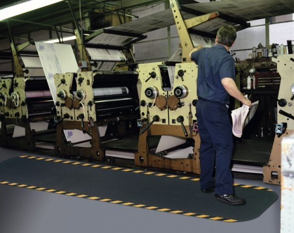 "Man standing on a Hog Heaven anti fatigue mat runner with Yellow Striped border in a 7/8"" floor mat thickness in front of a printing press"