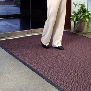 Man walking on a large door mat called Waterhog Masterpiece Select floor used as an indoor door mat to an office building