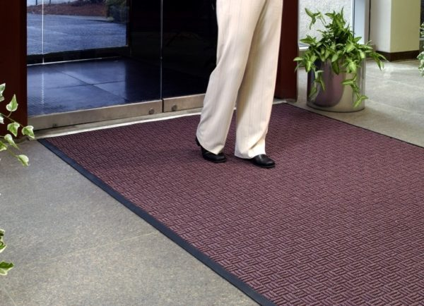 Man walking on a large door mat called Waterhog Masterpiece Select floor used as an indoor door mat to an office building