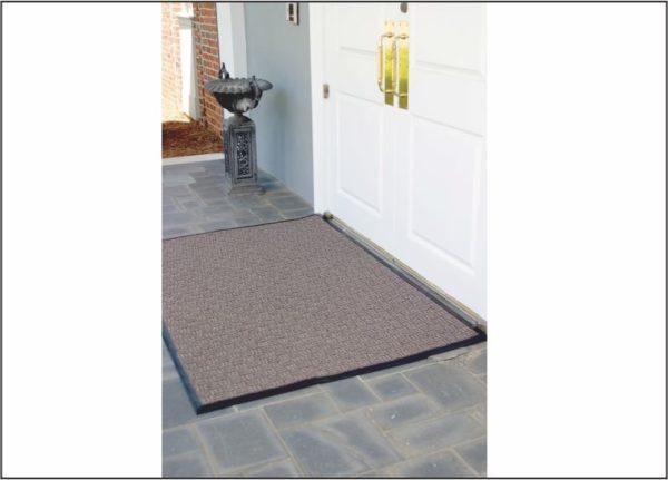 A large door mat called Waterhog Masterpiece Select floor used as an outdoor door mat under cover to an office building