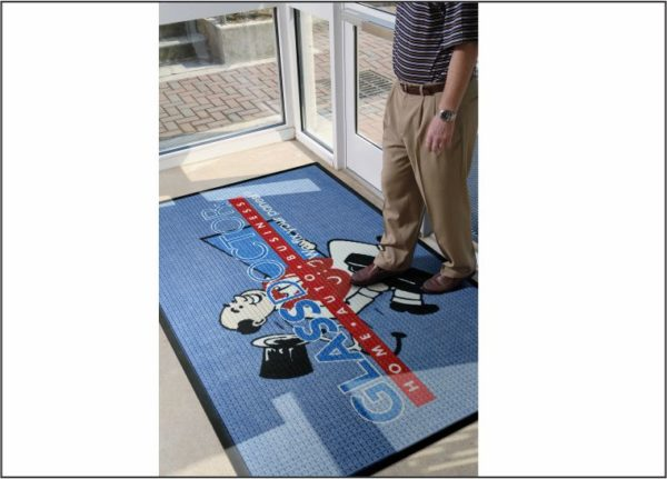 Man walking across a custom logo mat using the Waterhog Impressions logo mat process