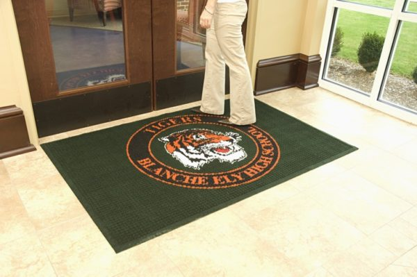 Waterhog Inlay custom logo mat with fashion borders with man walking over the mat at a high school entrance