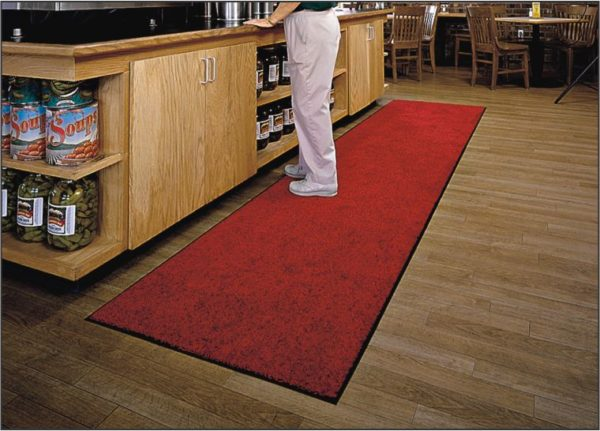 Man standing on a long Tri Grip floor mat runner in front of a food service counter