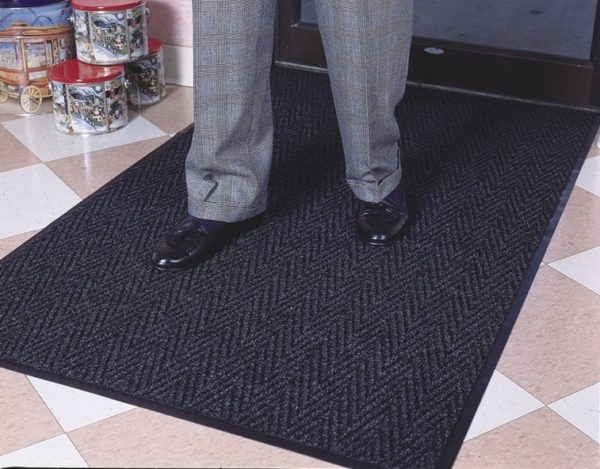 Man standing on Chevron indoor entrance mat placed inside main entrance to a retail store on a hard floor surface