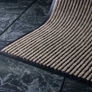Close up corner view of Dual Rib Walk off matting in a beige color showing the smooth vinyl edges and ribbed surface pattern