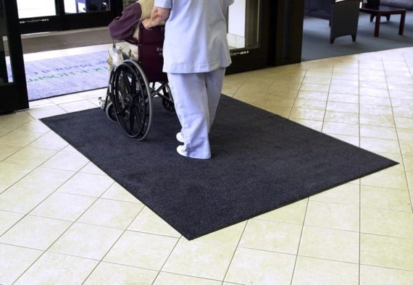 Wheelchair and nurse crossing over Stylist entrance mat placed as in indoor floor mat of a hospital