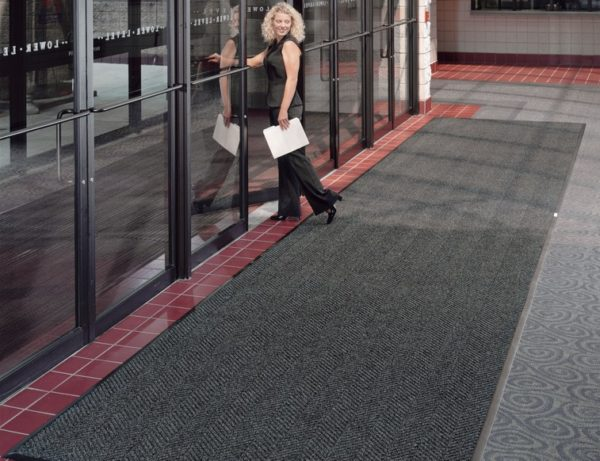 Woman walking across a large door mat placed at the interior entrance to a theatre