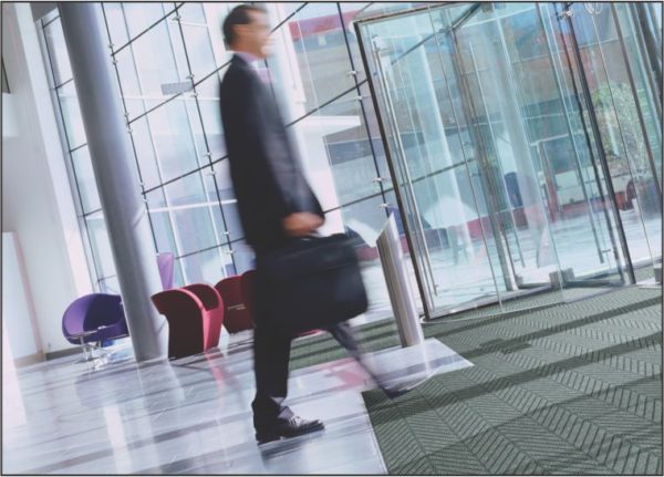 Businessman crossing over a recessed floor mat using Waterhog Eco Elite Roll goods in the entrance of a commercial building