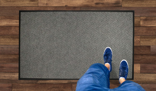 Aerial View of man standing on a Waterhog Classic Diamond carpet mat with standard rubber edges