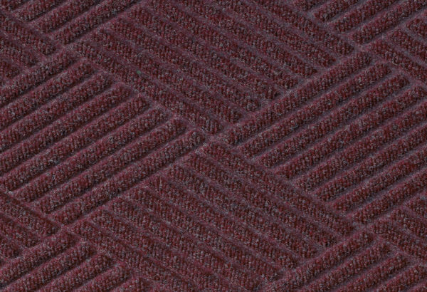 Close up surface view of Waterhog Eco Premier floor matting in a Maroon color