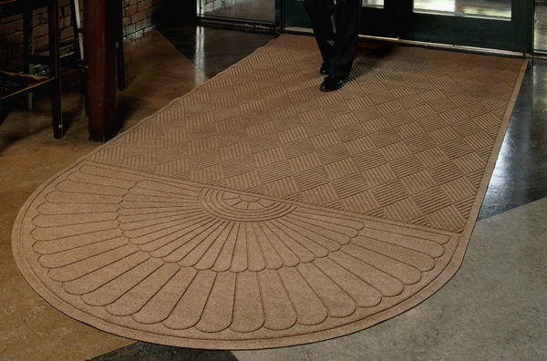 Man walking on a Waterhog Grand Classic Entrance Mat with an oval on one end used as an indoor door mat to a hotel