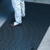 Man standing on a black diamondplate floor mat