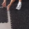 "Man with 3/8"" Interlocking Weight Room Flooring for Home Gyms showing easy Puzzle Interlock assembly"